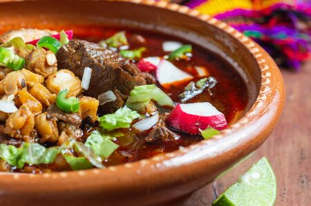 Mexican red pozole, hominy and pork stew seved with a variety of garnishes, such as onion, radish, cilantro, chili, lime and crispy tortillas.