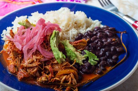 Cochinita Pibil, Mexican pit-roasted pork dish from Yucatan peninsula, served with rice, beans and traditional condiments. Tacos from Mexico.