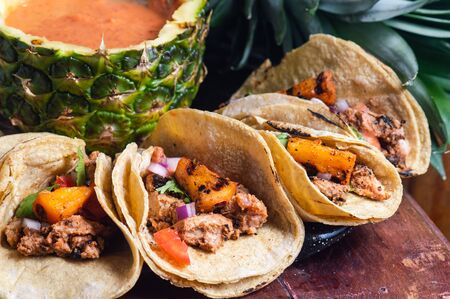 Tacos Al Pastor Shepherd's tacos, known as adobada tacos in the north of Mexico, spiced pork tacos with pineapple and spicy salsa Standard-Bild