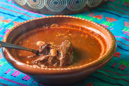 Traditional beef birria stew, Mexican food from Jalisco state. Served with fresh onion, cilantro and corn tortillas. A popular breakfast and hangover cure in much of Mexico