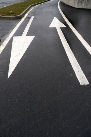 Asphalt road with  two opposite arrows photo