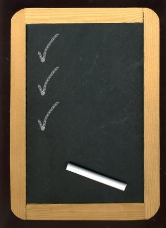 Image of little blackboard and chalk on black background Stock Photo