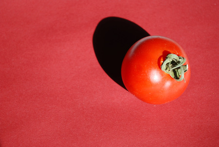 Tomato isolated on red background Stock Photo