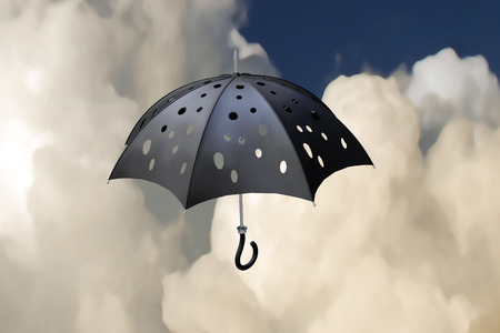 3d illustration flying pierced umbrella over storming sky background Stock Photo