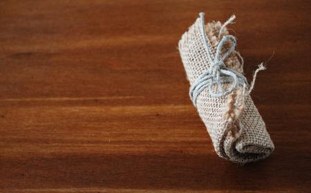 tiedup: Image of little canvas bundle on wood table