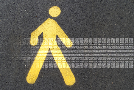 sign: Painted sign on asphalt for pedestrian lane and tire track. Concept: road hazards for pedestrians