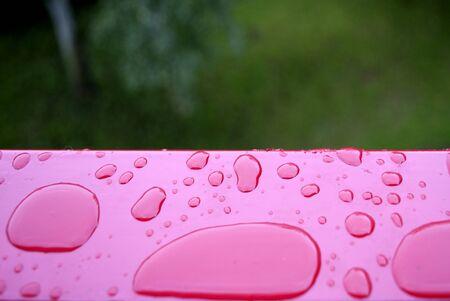 Rain drop layed on red metal plan