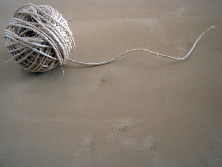 Close up of a roll of twine on woodden board Stock Photo