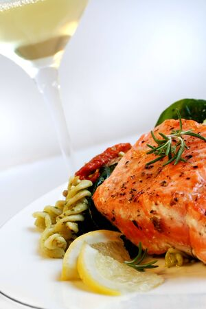 peppered: A grilled fillet of atlantic salmon, with fresh pasta salad and a glass of white wine.