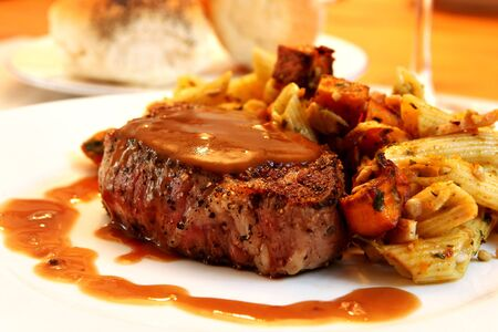 Filet Mignon beef steak with pasta vegetable salad.   Stock Photo