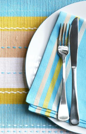 placemat: Place setting with silver fork and knife on pastel napkin, and matching placemat.  Vertical view.