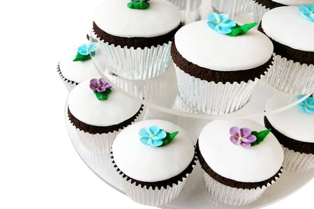 Fancy little cup cakes on a cake stand. Each is iced with royal icing and a flower, in a silver case. photo