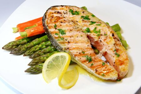 Salmon dinner, with asparagus,  carrots, and a parsley butter sauce.  Garnished with lemon. photo