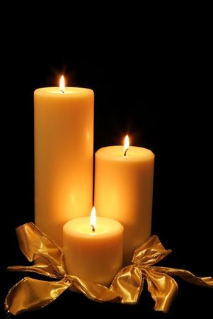 advent candles: Three Christmas candles glow in the darkness. Stock Photo