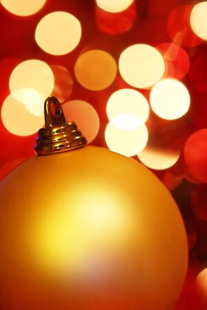defocussed: Golden Christmas bauble, with background of colorful defocussed lights. Stock Photo