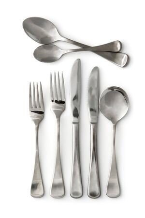 Silverware ~ stainless steel cutlery, casting shadow on clean white background.  Knives, forks, and spoons.