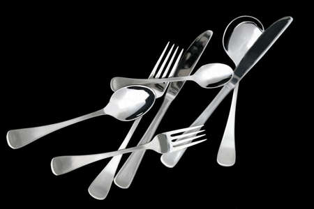 Scattered cutlery on black.  Knives, forks, and spoons. Stock Photo - 1928500