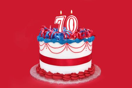 seventieth: 70th cake with numeral candles, on vibrant red background. Stock Photo