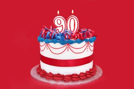 public celebratory event: 90th cake with numeral candles, on vibrant red background.