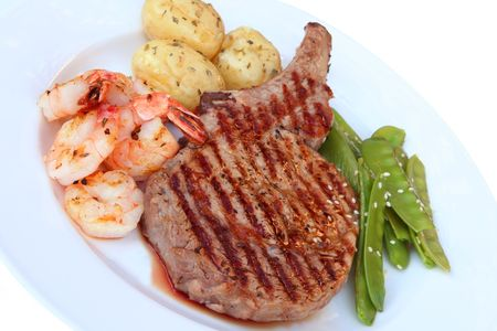 Rib-eye steak with shrimps and vegetables. photo