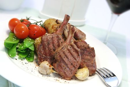 truss: Lamb cutlets with roasted potatoes and garlic, snowpeas, and cherry truss tomatoes.  Glass of red wine in the background, with shallow depth of field.