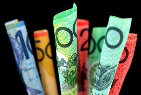 furled: Australian money ~ furled Australian notes, with black background.  Focus on front $100 note.