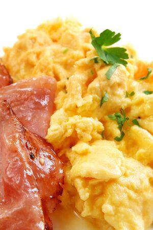 scrambled eggs: Huevos revueltos y tocino, con el perejil. Vista de cerca de un delicioso desayuno.