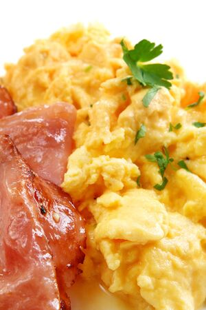 Scrambled eggs and bacon, with parsley.  Closeup view of a delicious breakfast.