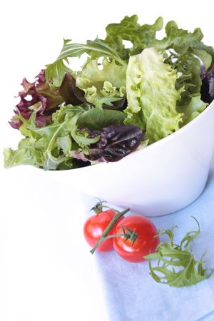 truss: Salad with mixed lettuce leaves and cherry truss tomatoes.  White bowl on pastel blue napkin.
