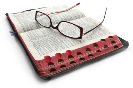 Open Bible with reading glasses.  Casting soft shadow on white. photo