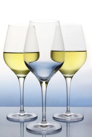 Naturally backlit wine glasses, two with white wine and one empty. photo