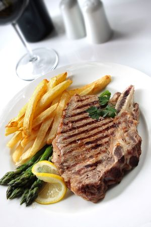 Steak and fries.  Home-made chips with grilled rib-eye beef steak and asparagus photo