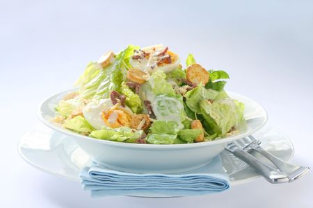 Caesar salad in white bowl.  Natural window light. photo