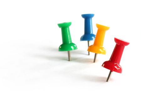 yellow pushpin: Pushpins in primary colors of red, green, yellow and blue.  Focus on front red pushpin. Stock Photo