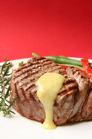 Thick filet mignon with bearnaise sauce, green beans and red peppers, and a sprig of rosemary.  Red background.