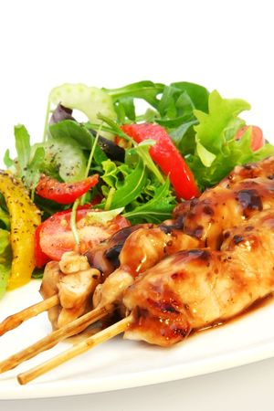 Delicious chicken satay skewers with fresh green salad. photo