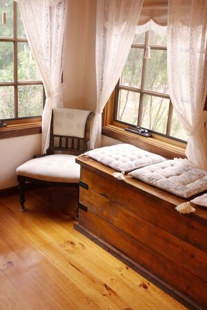 cushioned: Cosy corner of a Victorian country cottage, with cushioned window seat, and 19th century chair. Stock Photo