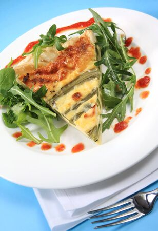 Asparagus quiche with salad and savoury sauce, with white napkin and fork. photo