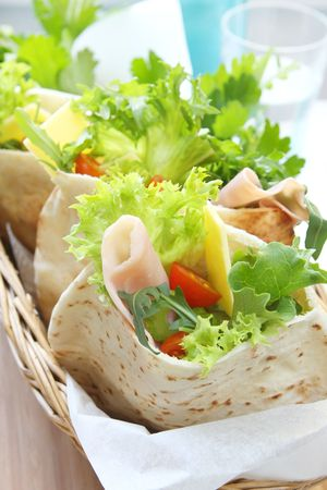 pita: A basket of pita bread pockets filled with ham and salad.  Healthy eating. Stock Photo