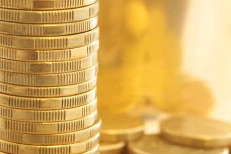 Gold coins in closeup, with golden light background.