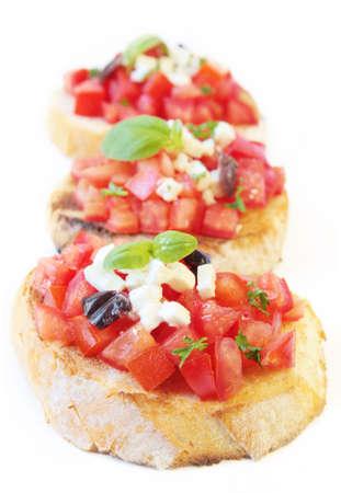 Bruschetta: Bruschetta with fresh vine tomatoes, olives, fetta cheese, and basil, on crostini.  Shallow DOF. Stock Photo