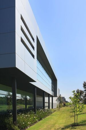 batiment industriel: Un industriel moderne, construction, avec des lits de jardins environnants et ciel bleu clair. Banque d'images