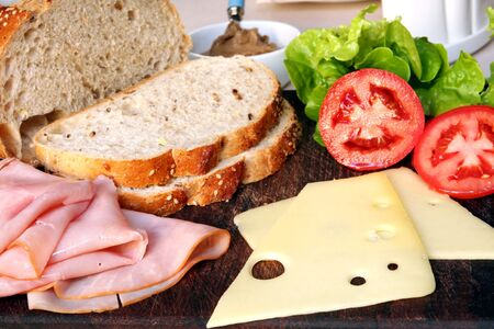wholegrain mustard: Sandwich in the making ~ fresh sliced sourdough wholegrain bread, ham, tomatoes, curly lettuce, and Jarlsberg cheese.  With mustard. Stock Photo