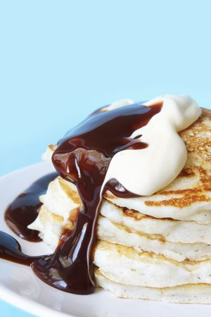 Pancakes covered with chocolate fudge sauce and fresh cream.  A delicious indulgence! Stock Photo - 1978311