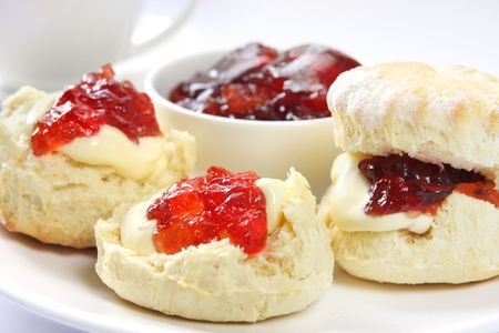 biscuits: Home-baked scones with strawberry jam and clotted cream, served with a cup of tea.  Known as a Devonshire tea. Focus on front scone.