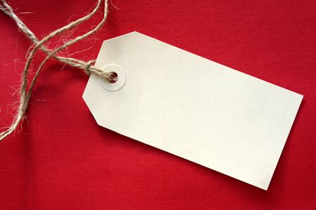 Blank tag tied with string, on vibrant red textured background. Stock Photo - 2031873