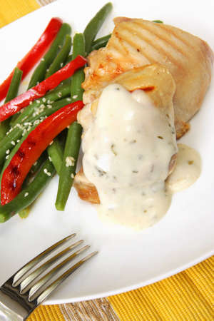 Grilled chicken with garlic and herb cream sauce, accompanied by green beans and grilled red capsicum.   photo