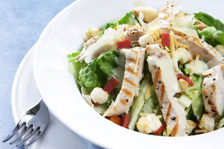Chicken Caesar salad with romaine lettuce, croutons, grated parmesan, bacon bits, and grilled chicken breast.  Delicious! photo