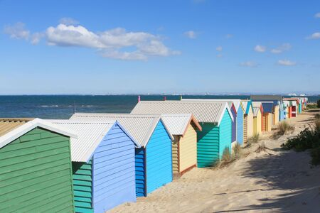 viewed from behind: Brightly-coloured bathing boxes at Brighton Beach, Melbourne, Australia.  Viewed from behind, overlooking Port Phillip Bay.