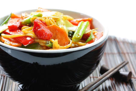 Stir-fried noodles and vegetables, in black bowl, with chopsticks.  Shallow DOF.
